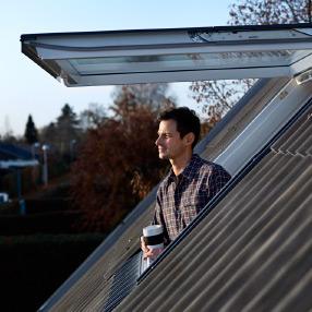 man enjoying coffee on rooftop through skylight