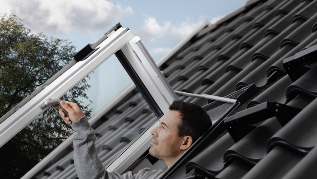 velux man pops through roof window