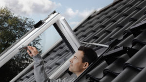 velux man pops through roof window