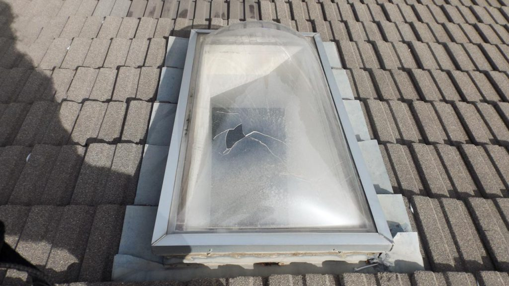Hail damaged curb mount skylight.